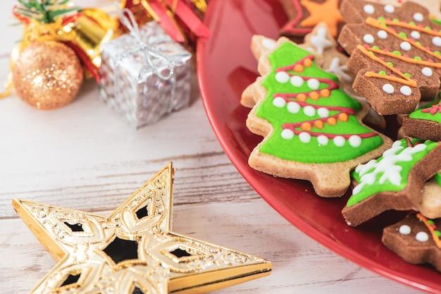 明るい木製のテーブルの背景に赤いプレートで美しいクリスマスの装飾が施された、おいしくてかわいい焼きたてのクリスマスクッキー(ジンジャーブレッド)、クローズアップ、コピースペース(テキストスペース)