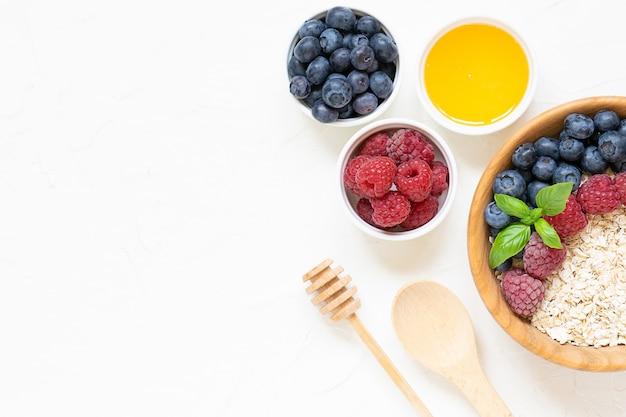 美味しくヘルシーな朝食のコンセプトです。果実と白いコンクリート背景上面に蜂蜜とコーンフレーク。