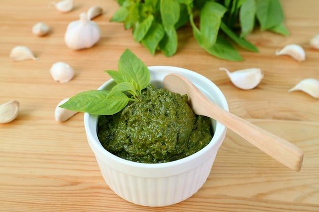 Вкусный и полезный домашний соус песто из свежего базилика в белой миске с деревянной ложкой