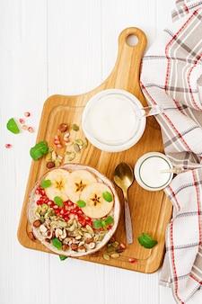 사과, 석류, 견과류와 함께 맛있고 건강 한 오트밀 죽. 건강한 아침 식사. 피트니스 음식. 적절한 영양 섭취. 평평하다. 평면도.
