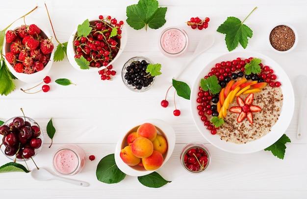 Вкусная и полезная овсяная каша с ягодами, семенами льна и смузи. здоровый завтрак. правильное питание. вид сверху. плоская планировка