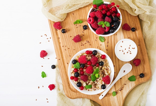Вкусная и полезная овсяная каша с ягодами, семенами льна и йогуртом. здоровый завтрак. правильное питание. квартира лежала. вид сверху.