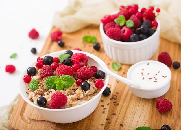 Вкусная и полезная овсяная каша с ягодами, семенами льна и йогуртом. здоровый завтрак. правильное питание