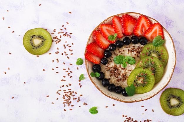 Вкусная и здоровая овсяная каша с фруктами, ягодами и семенами льна.