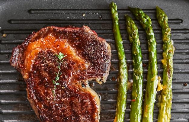 Вкусный и сочный стейк и спаржа, наполовину обжаренные на сковороде и посыпанные тертым сыром пармезан