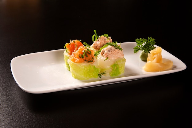 Tasty appetizer sushi roll with cabbage, salmon and cheese.