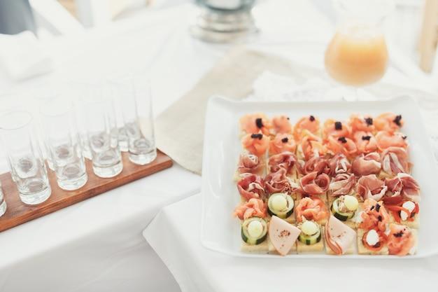 四角いプレート上で魚や野菜のおいしい前菜