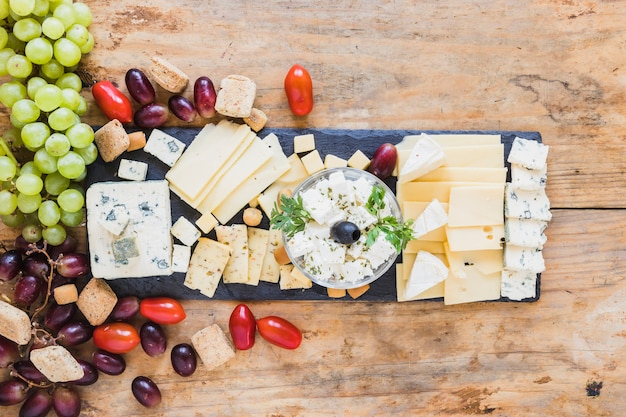 Tasty appetizers with cheese plate, tomatoes and grapes