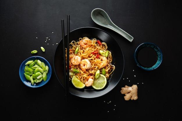 暗い表面のプレートに野菜とエビを添えたおいしい食欲をそそるアジアンヌードル