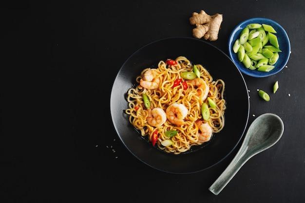 Вкусная аппетитная азиатская лапша с овощами и креветками на тарелке на темной поверхности