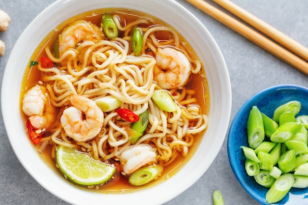 Tasty appetizing asian noodles with vegetables and shrimps in bowl on concrete surface