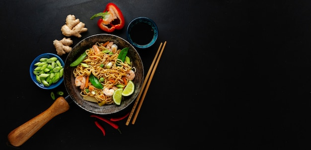 Tasty appetizing asian noodles with vegetables and shrimps on pan on dark surface