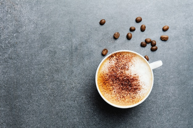Tasty appetizing cappuccino in cup with beans on concrete table.
