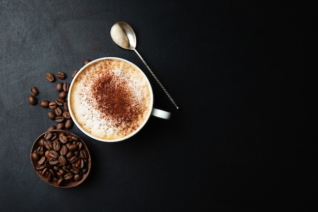 Tasty appetizing cappuccino in cup with beans on dark table.