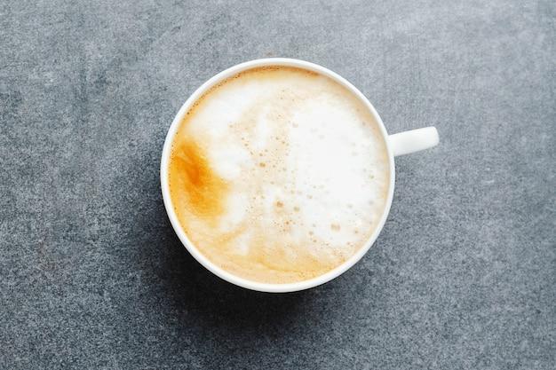Вкусный аппетитный капучино в чашке с фасолью на бетонном столе.