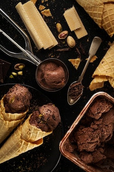 Tasty appetizing chocolate ice cream with mint and pistachios in small cones on dark background. cooking process. top view.