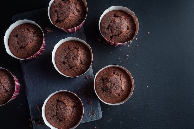Tasty appetizing chocolate muffins in cups on dark background.