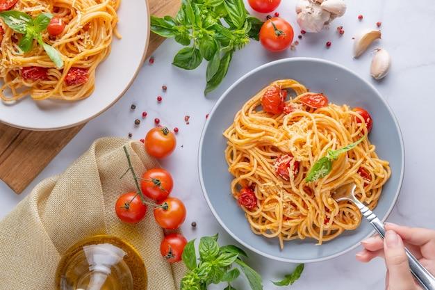 トマトソース、チーズパルメザン、バジルを皿に盛り、白い大理石のテーブルでパスタを調理するための食材を使った、食欲をそそるクラシックなイタリアンスパゲッティパスタフラット レイ トップ ビュー コピー スペース。