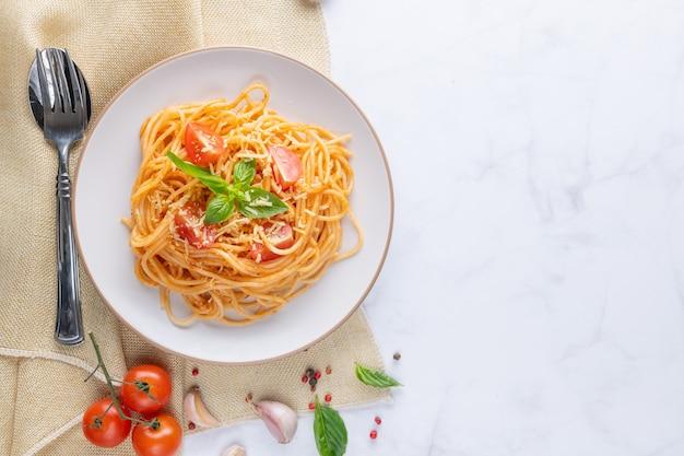 Gustosi e appetitosi spaghetti italiani classici con salsa di pomodoro, parmigiano e basilico sul piatto e ingredienti per cucinare la pasta sul tavolo di marmo bianco. spazio di copia vista dall'alto piatto.