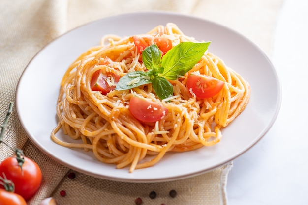 Tasty appetizing classic italian spaghetti pasta with tomato sauce, cheese parmesan and basil on plate and ingredients for cooking pasta on white marble table.