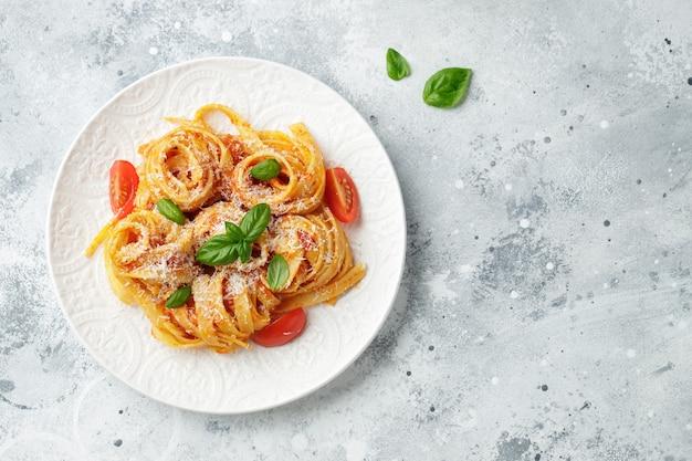 ライトテーブルのプレートにトマトソース、チーズパルメザンチーズ、バジルを添えた、おいしい食欲をそそるクラシックなイタリアのタリアテッレパスタ。上からの眺め、水平。コピースペースのある上面図。