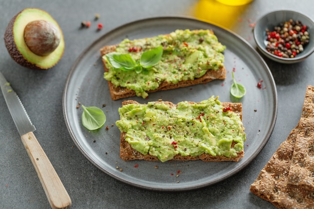 На тарелке подают вкусные аппетитные хрустящие хлебцы с пюре из авокадо.