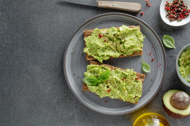 Tasty appetizing crispbread with mashed avocado served on plate.