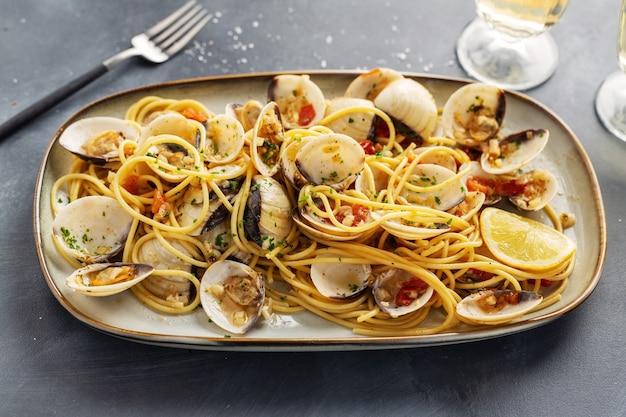 맛있는 식욕을 돋우는 신선한 수제 조개는 마늘과 접시에 화이트 와인을 곁들인 봉골레 해산물 파스타를 모두 포함합니다. 확대.