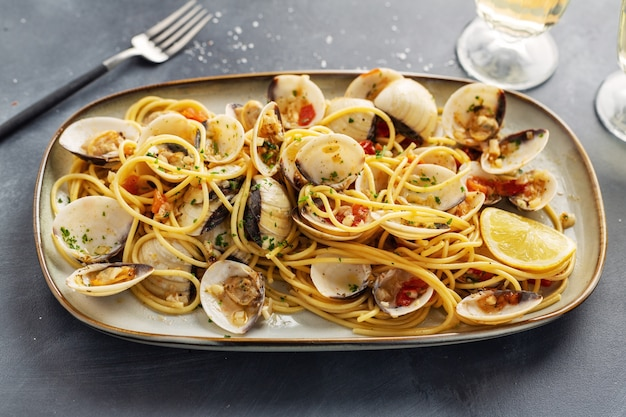 Tasty appetizing fresh homemade clams alle vongole seafood pasta with garlic and white wine on plate. closeup.