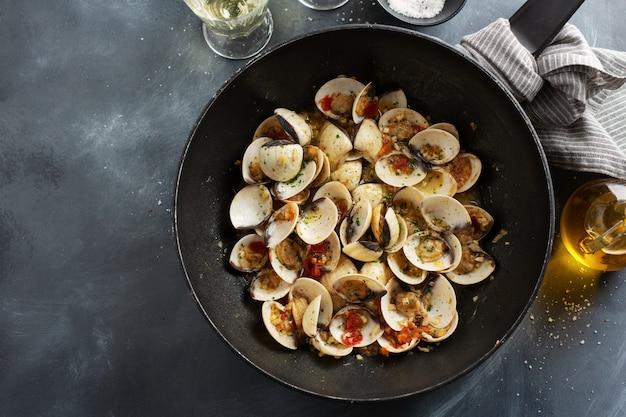Вкусные аппетитные свежие домашние моллюски алле вонголе с чесноком и белым вином на сковороде. вид сверху.
