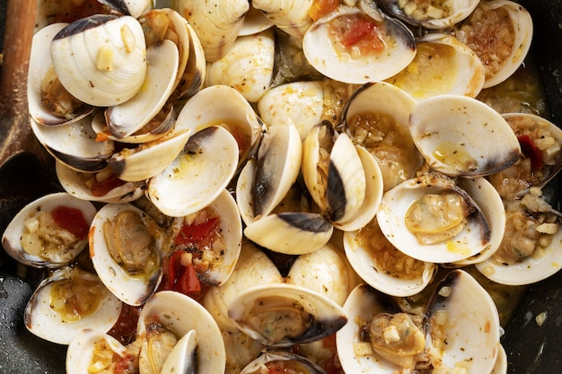 Tasty appetizing fresh homemade clams alle vongole with garlic and white wine on pan. closeup.