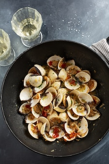 Tasty appetizing fresh homemade clams alle vongole with garlic and white wine on pan. top view.
