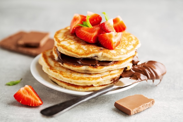 Tasty appetizing freshmade pancakes decorated with strawberry and chocolate paste served for breakfast. closeup