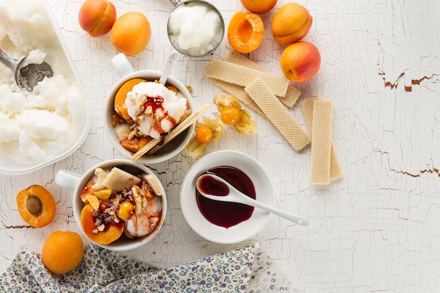 Tasty appetizing ingredients for cooking vanilla ice cream with ice cream spooons and fruits. top view with copy space.