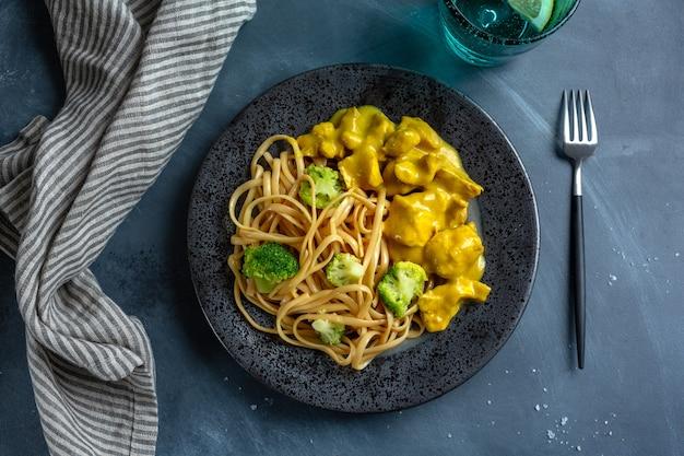 카레 소스에 닭고기 덩어리를 곁들인 맛있는 식욕을 돋우는 국수 스파게티 우동이 접시에 제공됩니다. 확대.