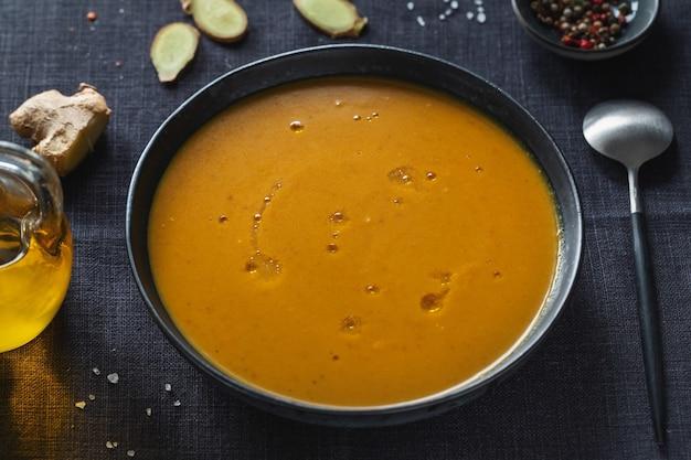 Вкусный аппетитный восточный суп из тыквы и чечевицы с имбирем в миске. крупным планом