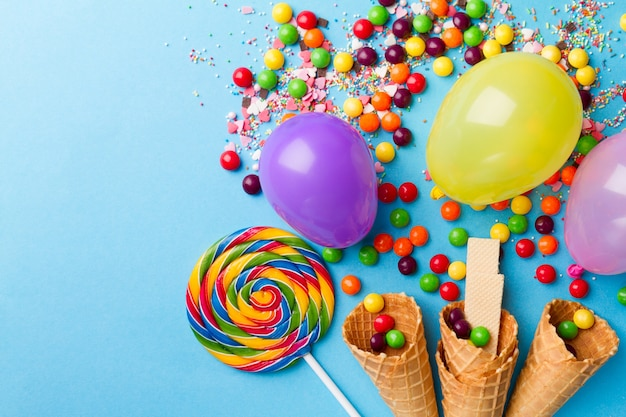 Tasty appetizing party accessories on bright blue background