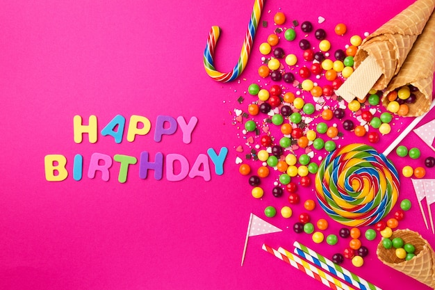Tasty appetizing party accessories happy birthday on bright pink background