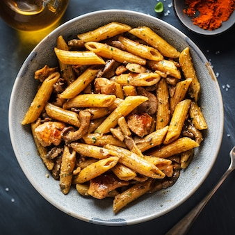 Tasty appetizing pasta penne with mushrooms in sauce. served on plate.  square