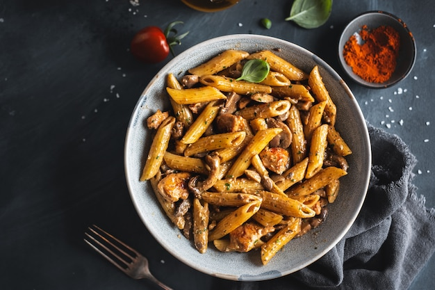 Tasty appetizing pasta penne with mushrooms in sauce. served on plate.