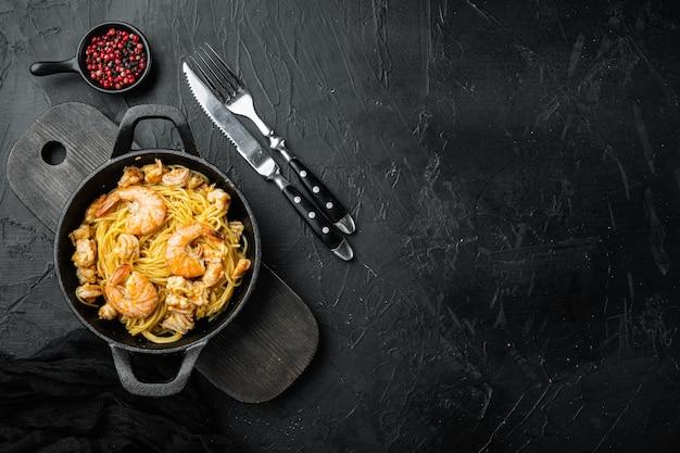 검은 돌에 페스토 소스와 새우 세트를 곁들인 맛있는 식욕을 돋우는 파스타 스파게티