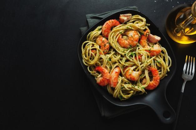 새우와 페스토 소스를 곁들인 맛있는 식욕을 돋우는 파스타가 어두운 접시 팬에 제공됩니다. 위에서 봅니다.
