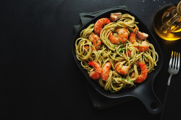 Tasty appetizing pasta with shrimps and pesto sauce served on dark plate pan. view from above.