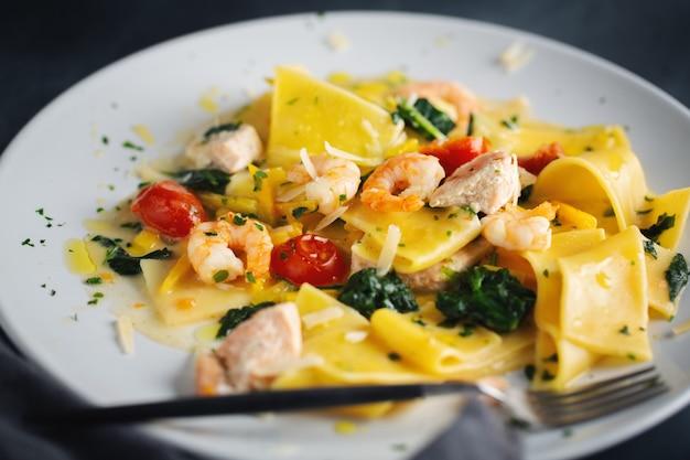 Вкусная аппетитная паста с креветками, овощами и шпинатом подается на тарелке. крупный план.
