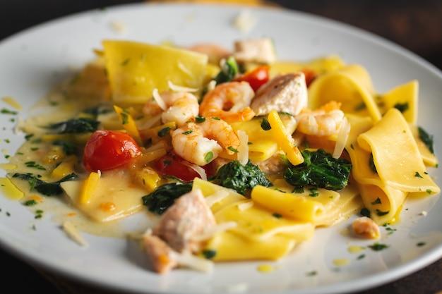 Вкусная аппетитная паста с креветками, овощами и шпинатом подается на тарелке.