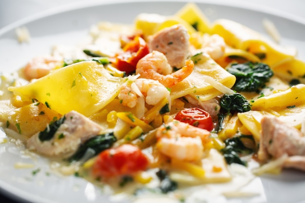 Tasty appetizing pasta with shrimps, vegetables and spinach served on plate.