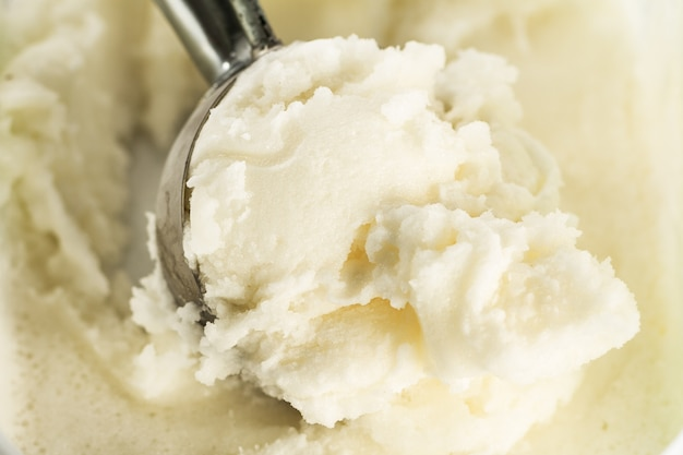 Tasty appetizing pure vanilla creamy ice cream with in ice cream spoon. closeup. horizontal with copy space.