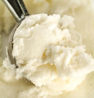 Tasty appetizing pure vanilla creamy ice cream with in ice cream spoon. closeup.