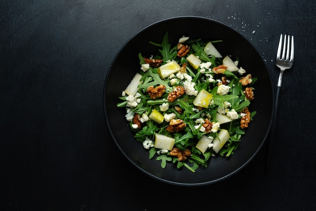 Tasty appetizing salad with pear, blue cheese, walnuts, arugula served on dark plate.