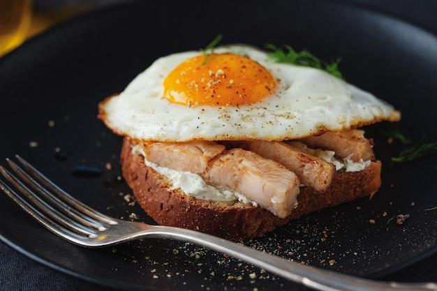 Вкусный аппетитный бутерброд с кусочками курицы и жареным яйцом на тарелке на темной поверхности